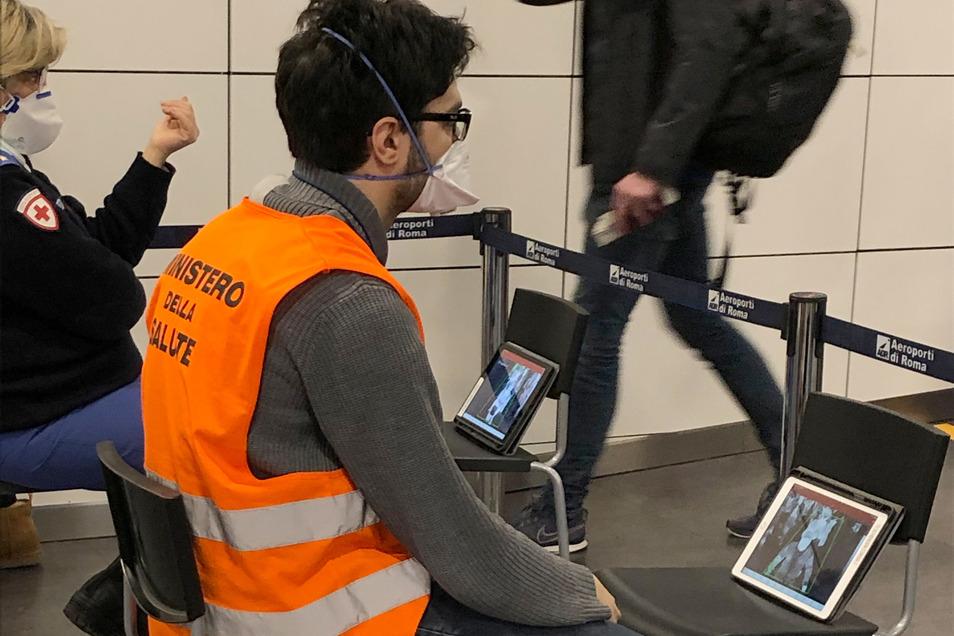 Mitarbeiter des Gesundheitsministeriums beobachten die Einreise am Flughafen Fiumicino in Rom. Das Coronavirus Sars-CoV-2 breitet sich in Europa weiter aus.