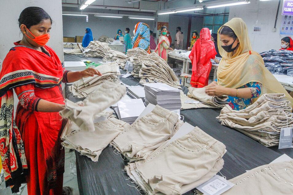 In Bangladesch wird Kleidung nicht nur wegen Corona mit Mundschutz sortiert. Wann schaffen es internationale Unternehmen endlich, die Arbeitsbedingungen zu standardisieren.