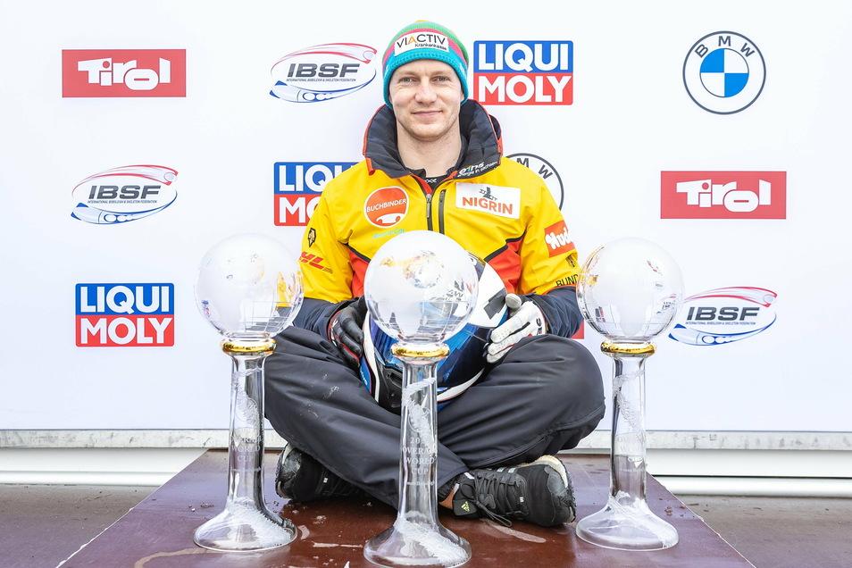 Der Pilot aus Pirna und seine nächsten Pokale: Francesco Friedrich posiert mit den drei Pokalen für die Gesamtweltcupsiege im Zweier- und Viererbob sowie in der Kombinationswertung.