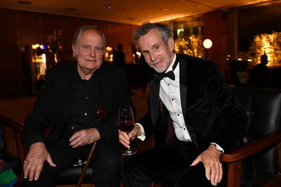 Ulrich Matthes (r.) sitzt bei der Filmpreis-Party zusammen mit dem Regisseur Paul Verhoeven.