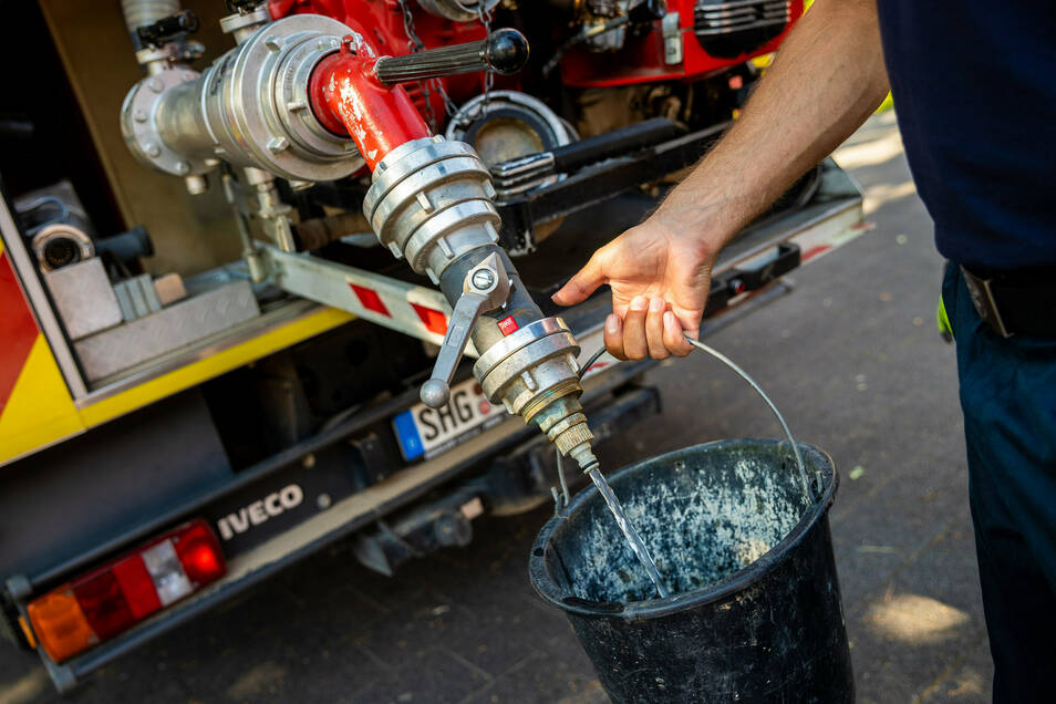 Einsatzkräfte der Freiwilligen Feuerwehr Lauenau zapfen Löschwasser aus dem Tank eines ihrer Einsatzfahrzeuge.