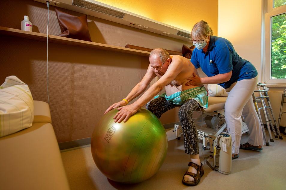 Therapeutin Silvana Mohr macht mit dem Post-Covid-Patient Josef Käsz in den Fachkliniken für Geriatrie in Radeburg eine Atem-Dehn- Übung.