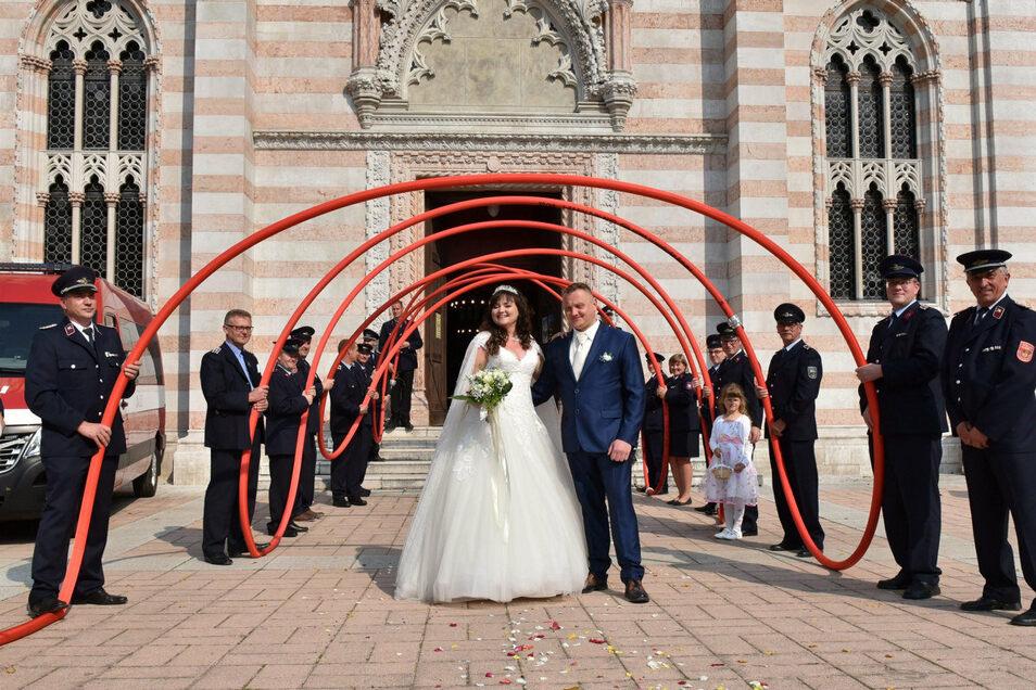 Die Kameraden der freiwilligen Feuerwehr von Zinnwald-Georgenfeld und Altenberg bilden vor der Kirche in Dubí ein Spalier für das Hochzeitspaar Gabriela und André Forkel.