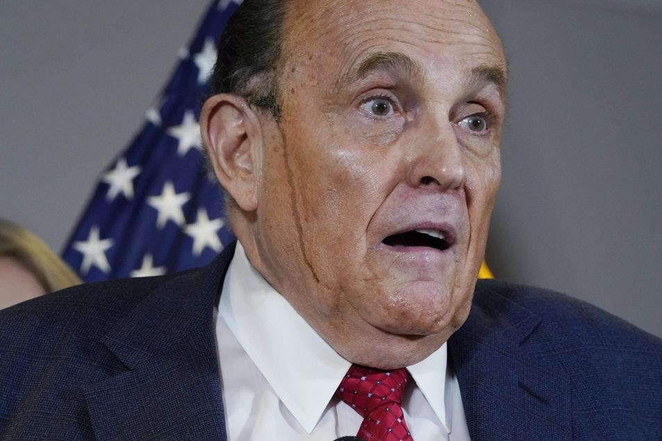 Rudy Giuliani läuft Haarfärbemittel von den Haaren die Wange herunter.