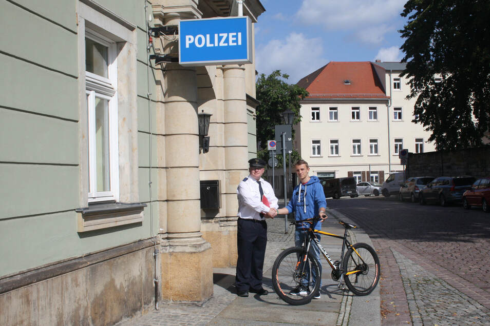 Polizist Daniel Szenes übergibt einem jungen Mann ein Fahrrad, das ihm in Dresden gestohlen wurde. Der Verdächtige wurde von einer Pirnaer Polizistin entdeckt und überführt.