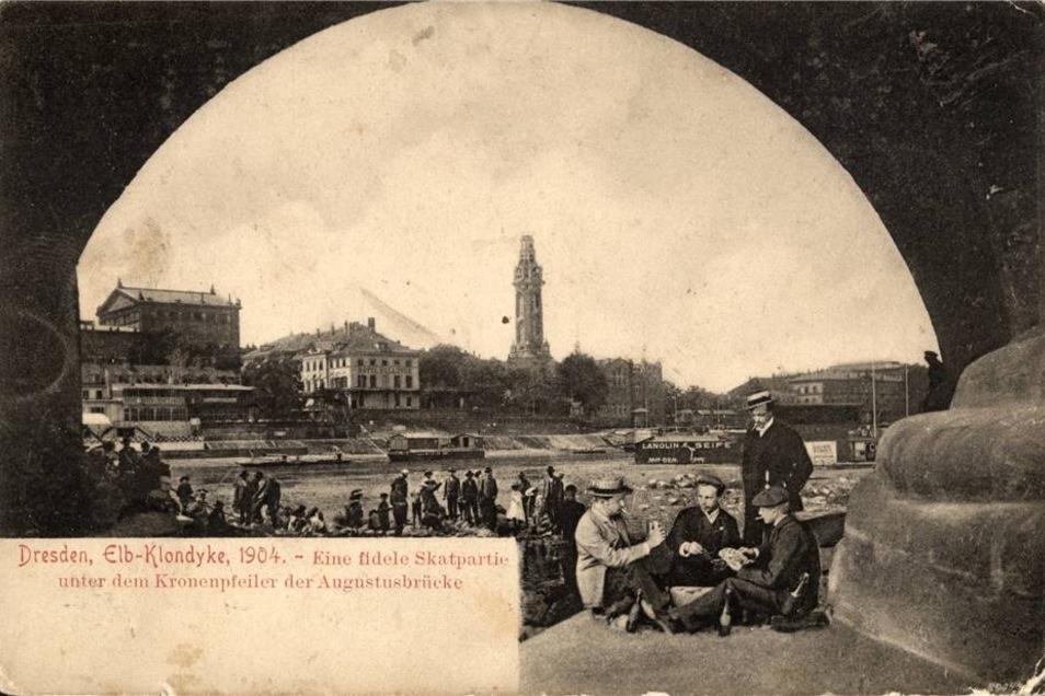 Diese Postkarte zeigt eine Skatpartie unter der Augustusbrücke.