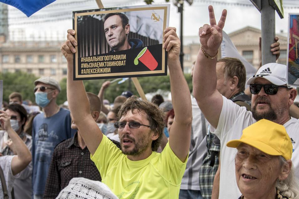 """Russland, Khabarovsk: Ein Mann hält bei einer Demonstration ein Plakat mit einem Porträt von dem Oppositionsführer Alexej Nawalny, auf dem zu lesen ist: """"Nawalny wurde vergiftet, wir wissen, wer schuld ist, Alexej du musst leben""""."""