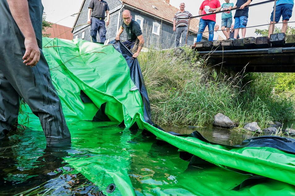 Danach wird eine der drei mobilen Wassersperren ins Landwasser in Oderwitz gezogen.