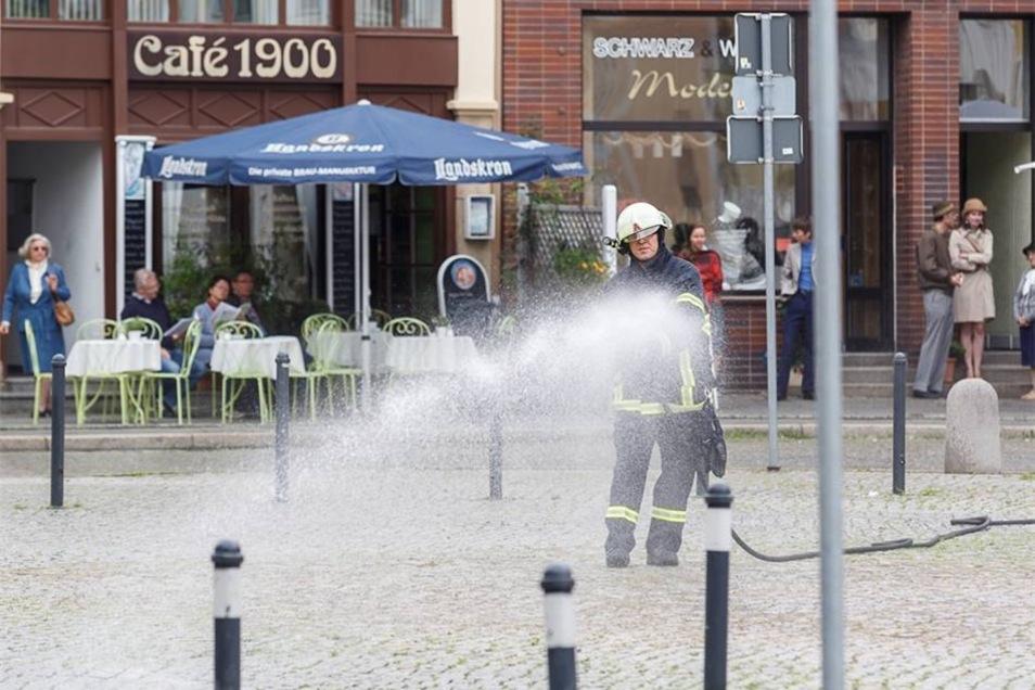 Ein Feuerwehrmann befeuchtet für die nächste Szene den Obermarkt.