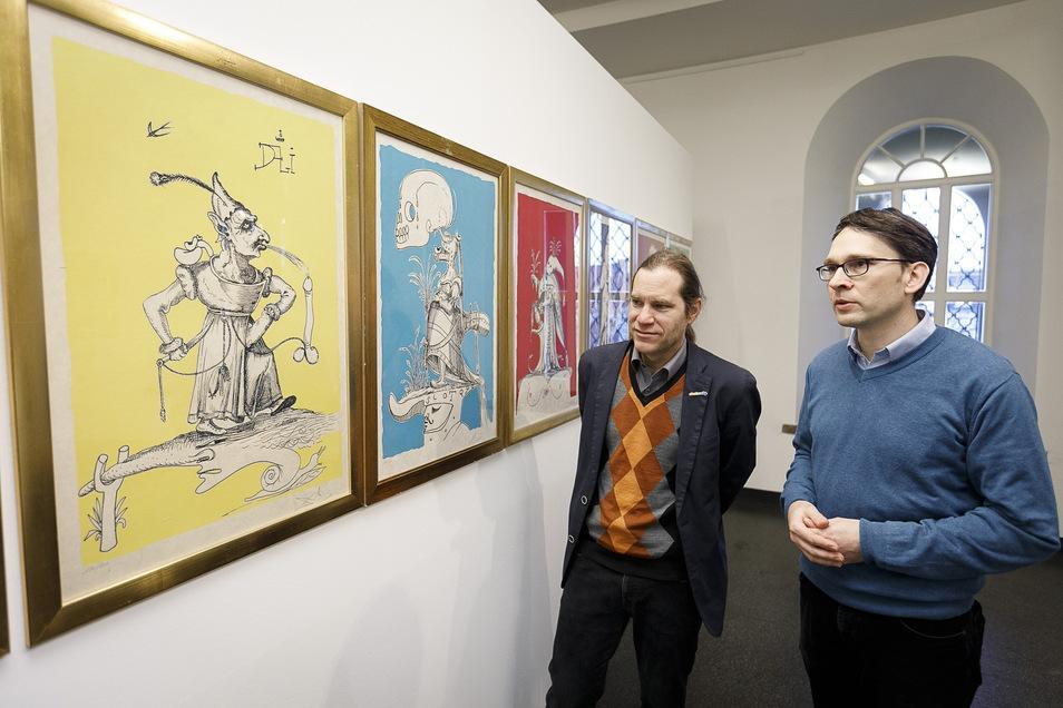 Viele sehr farbige Grafiken zeigen Kurator Kai Wenzel (r.) und Peter Knüvener in der Dalí-Ausstellung.