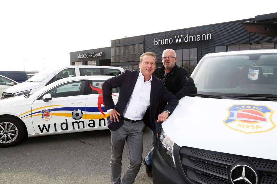 Jens Bergk (l.), Geschäftsführer des Autohauses Widmann in Zeithain, und Falko Obenaus, Geschäftsführer der Stahl Riesa Sport GmbH, vor den drei neuen Autos für die BSG Stahl Riesa.