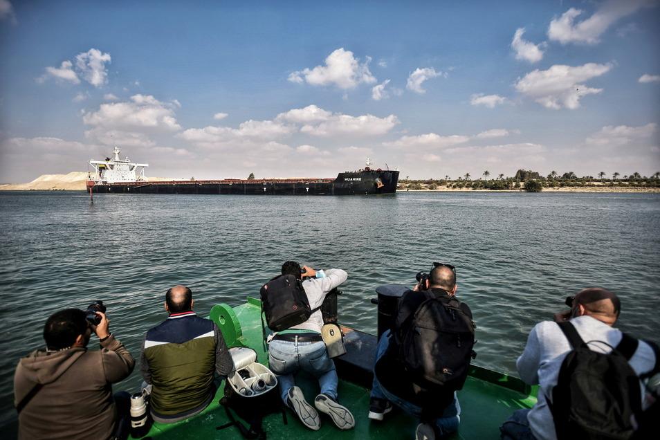 Ägypten, Ismailia: Fotografen machen Bilder von einem Schiff, das durch den Suezkanal fährt.