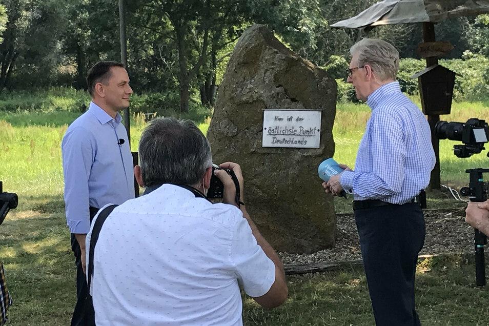 So begrüßten sich AfD-Chef Tino Chrupalla (li.) und ZDF-Reporter Theo Koll am östlichsten Punkt Deutschlands.