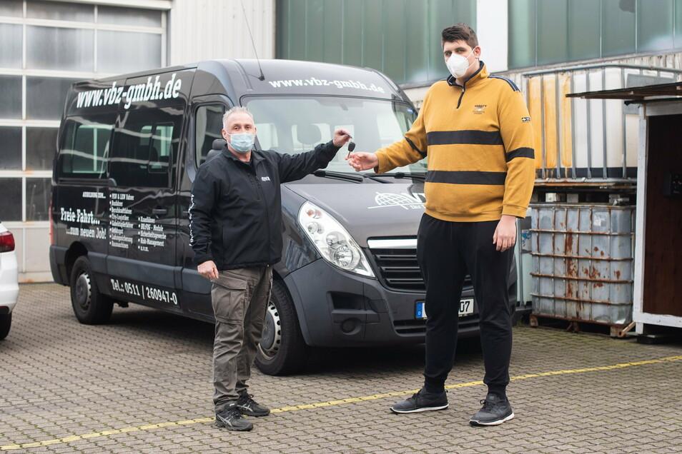 Jannik Könecke (r) und Fahrlehrer Jörg Vespermann stehen vor einem für große Fahrschüler umgebauten Fahrzeug.