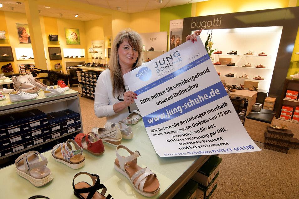 Das Plakat, das Annett Jung zeigt, wird ab Donnerstag am geschlossenen Schuhgeschäft hängen. Es weist auf die Möglichkeit für den Einkauf im Internet hin.