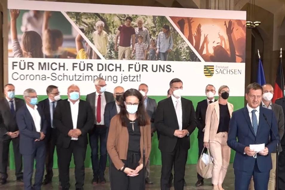 Sachsens Ministerpräsident Michael Kretschmer (r) trat nach dem Impfgipfel mit allen Teilnehmern vor die Presse.