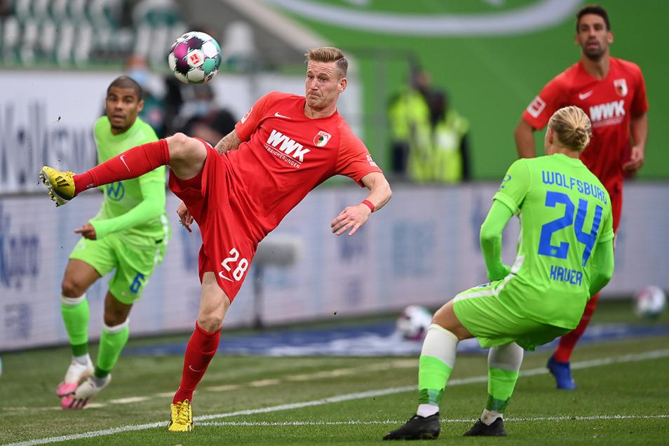 Augsburgs Andre Hahn (l) spielt gegen Wolfsburgs Xaver Schlager.
