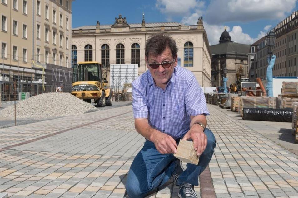 Straßenbauamtsleiter Reinhard Koettnitz zeigt einen der Natursteine, die verlegt werden.