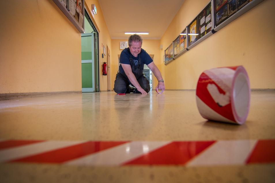 Auch der Boden wird an der Oberschule Waldheim mit Abstandsmarkierungen versehen. Hausmeister Jürgen Hofmann klebt Abstandsstreifen auf den Fußboden