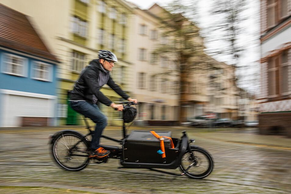 Wenn man das Lenken geübt hat, gehts auch in der Kurve recht sportlich voran: Frank Sinapius auf seinem Lasten-Fahrrad.