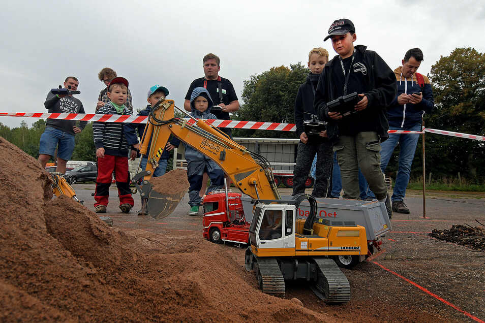 Marco Felgner (hinten links im Gespräch) hat bei den ersten Harthaer Modelltagen bewiesen, dass Modellfahrzeuge durchaus etwas bewegen können. In diesem Fall waren es mehrere Kubikmeter Sand.