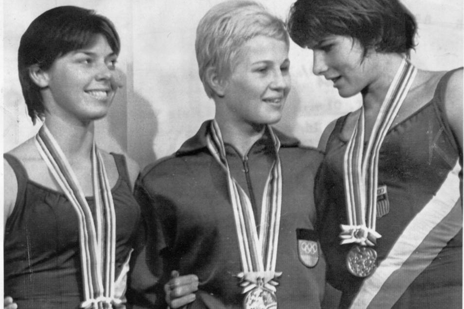 Bei den Olympischen Sommerspielen in Tokio 1964 gewinnt Ingrid Engel-Krämer (M./später Gulbin) die Goldmedaille im Wasserspringen. Nach der feierlichen Siegerehrung unterhält sie sich auf dem Podium mit Jeanne Collier (l./Silber, USA) und Mary Willard (Br