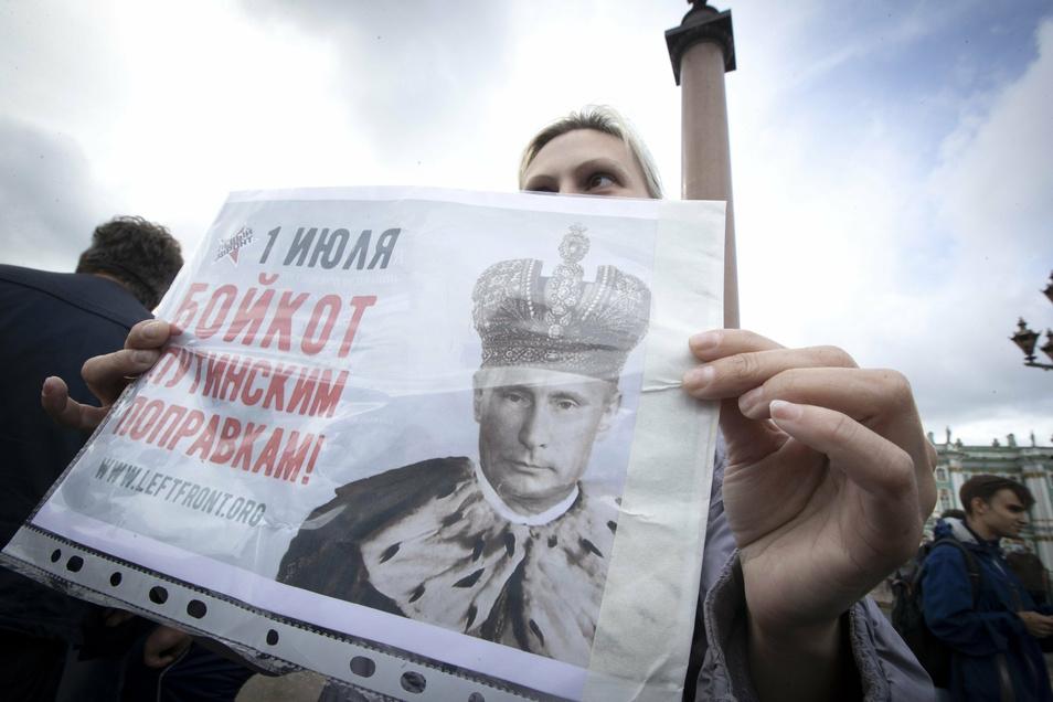 Eine Frau hält bei einem Protest gegen die Verfassungsänderung auf dem Palastplatz in St. Petersburg ein Plakat mit dem Bild des russischen Präsidenten als König hoch.