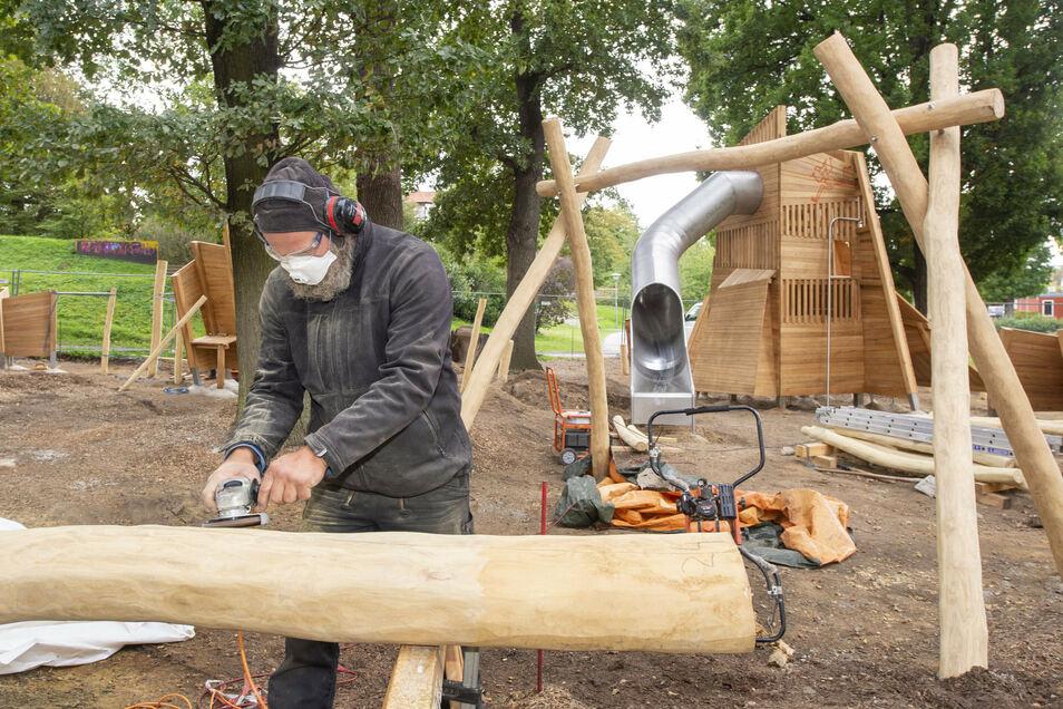 Jan Hutschenreuter von der Firma Grasreiner-Design aus Dresden schleift einen Robinienpfosten für den neuen Spielplatz Faunhöhle.