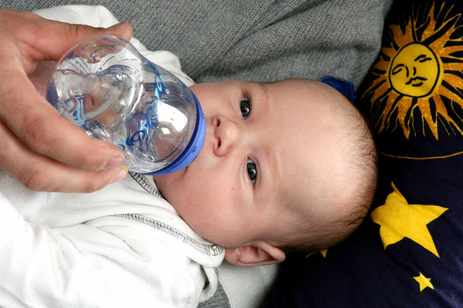 Ein Vater gibt seinem sieben Wochen alten Sohn eine Nuckelflasche gefüllt mit Tee.