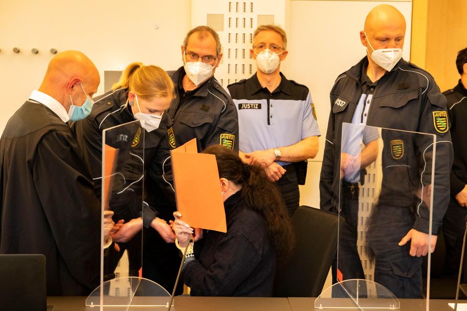Die Hauptangeklagte Stefanie W. (sitzend), hier mit ihrem Verteidiger Oliver Nießing (l.) und umringt von Justizbediensteten, soll für den Tod ihres Ehemannes verantwortlich sein. Sie schweigt in dem Prozess am Landgericht Dresden.