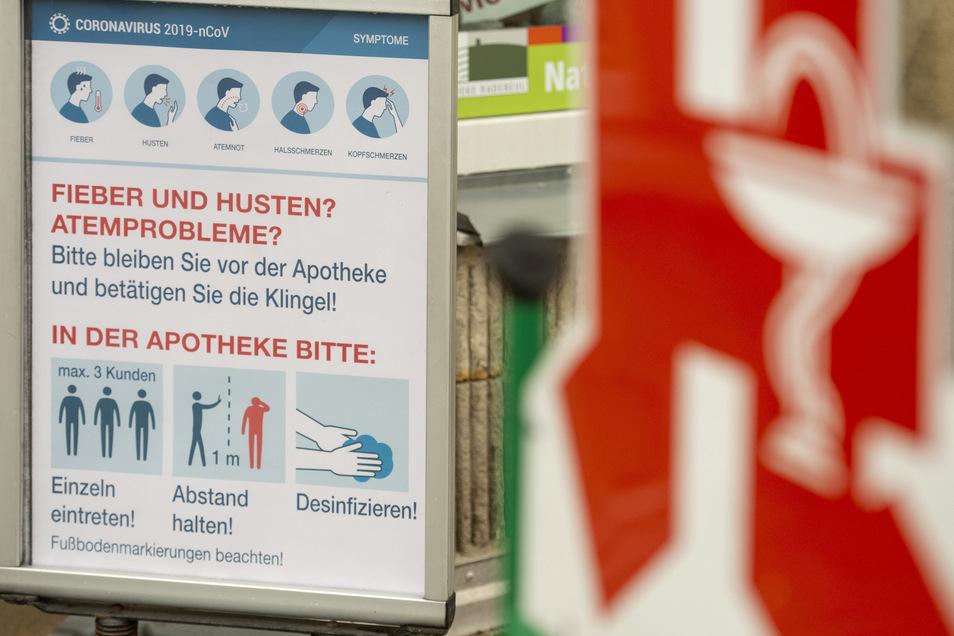 Vor dem Eingang - ein Plakat sagt in Weinböhla und Radebeul den Patienten, wie sie handeln sollen, bevor sie die Apotheke betreten.