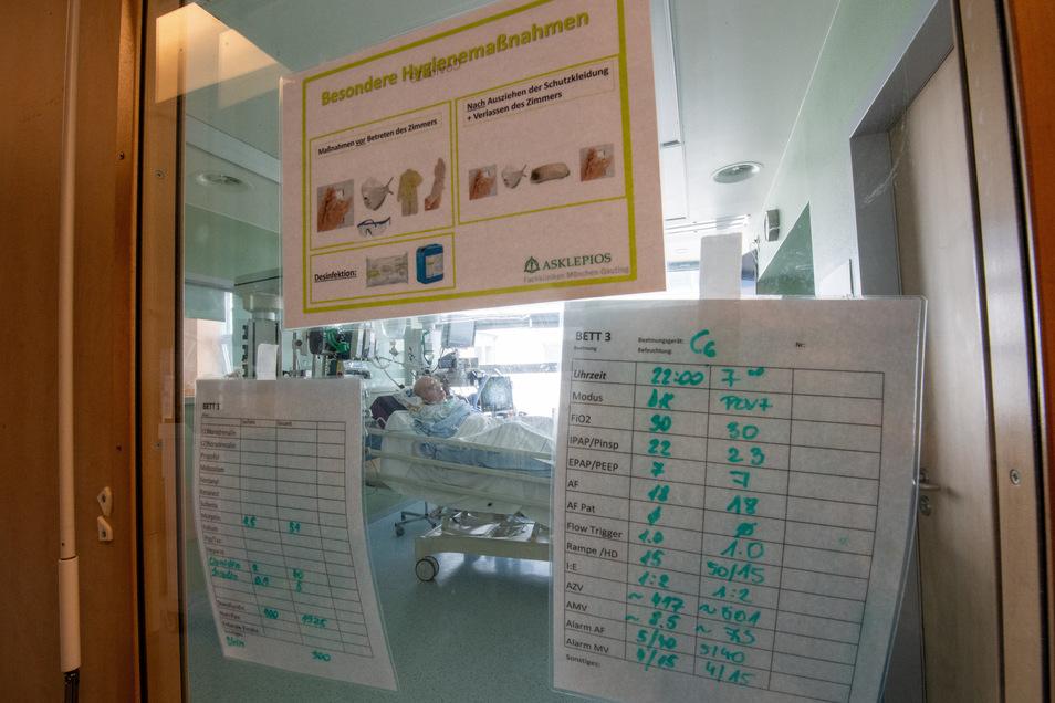 Ein positiv getesteter Corona-Patient liegt in einem isoliertem Intensivbett-Zimmer in einer Klinik im bayerischen Gauting.