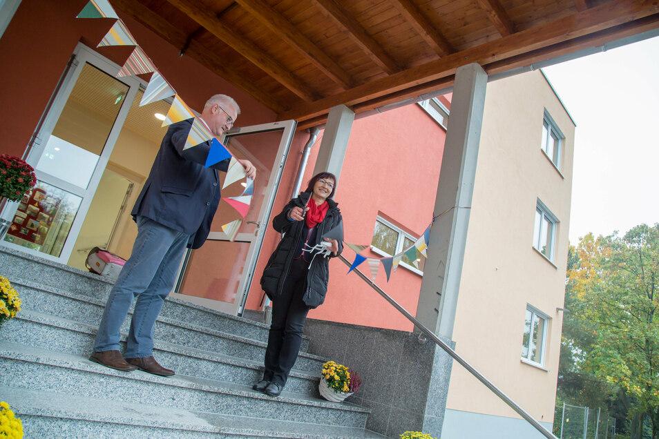 Bürgermeister René Schöne gibt die Schere an Schulleiterin Kathrin Engelmann weiter. Sie durchschnitt die Wimpelkette und nahm damit den Anbau an die Oberschule in den Besitz der Lehrer und Schüler.