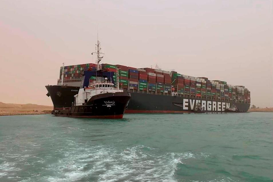 Ein Schlepper zieht das Frachtschiff.