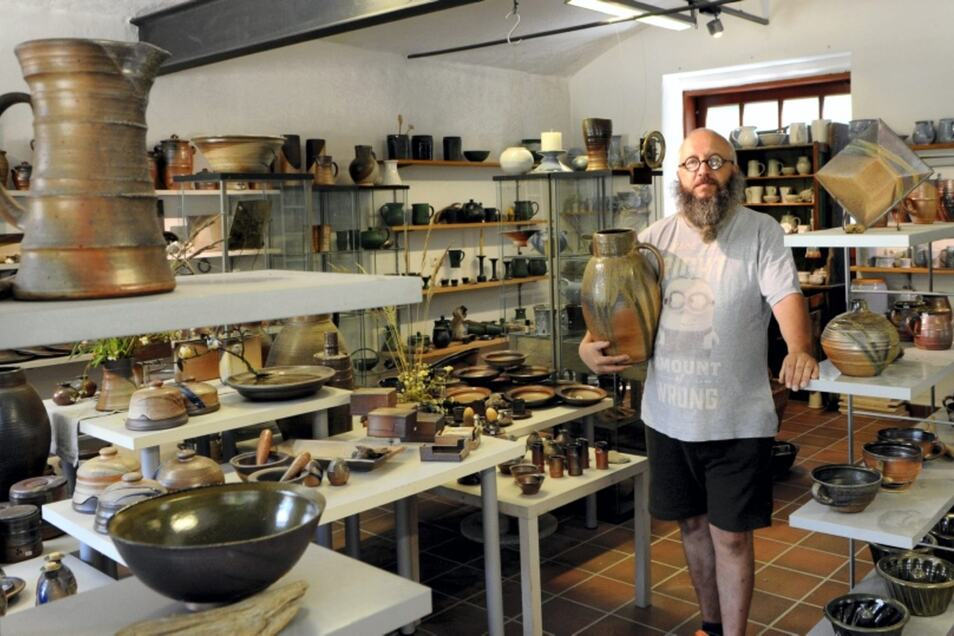 Töpfer Gordon Gran hält eine Kanne, die er – angelehnt an die typische Muskauer Form – hergestellt hat. Kannen und anderes Gebrauchsgeschirr verkauft er im Werkstatt-Laden im Pückler-Park.