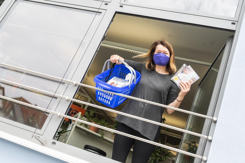 Mit dem Körbchen durchs Fenster: Bibliothekarin Birgit Herold zeigt, wie man ab dem 27. April aus der Riesaer Bibliothek Bücher ausleihen kann.