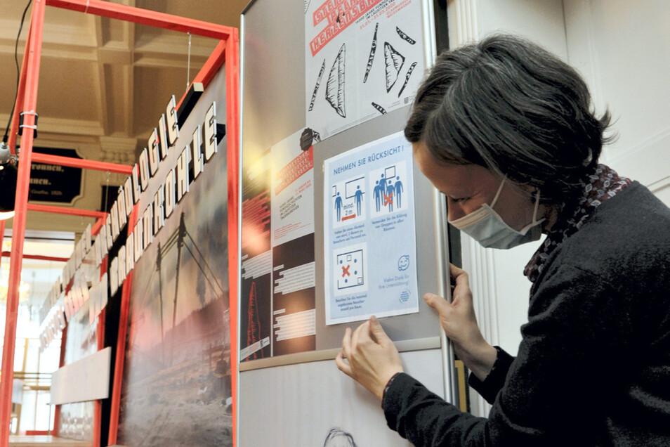 Christine Lehmann bringt im Glasmuseum Weißwasser wie gefordert die Hinweise zum Verhalten der Besucher in Zeiten von Corona an.