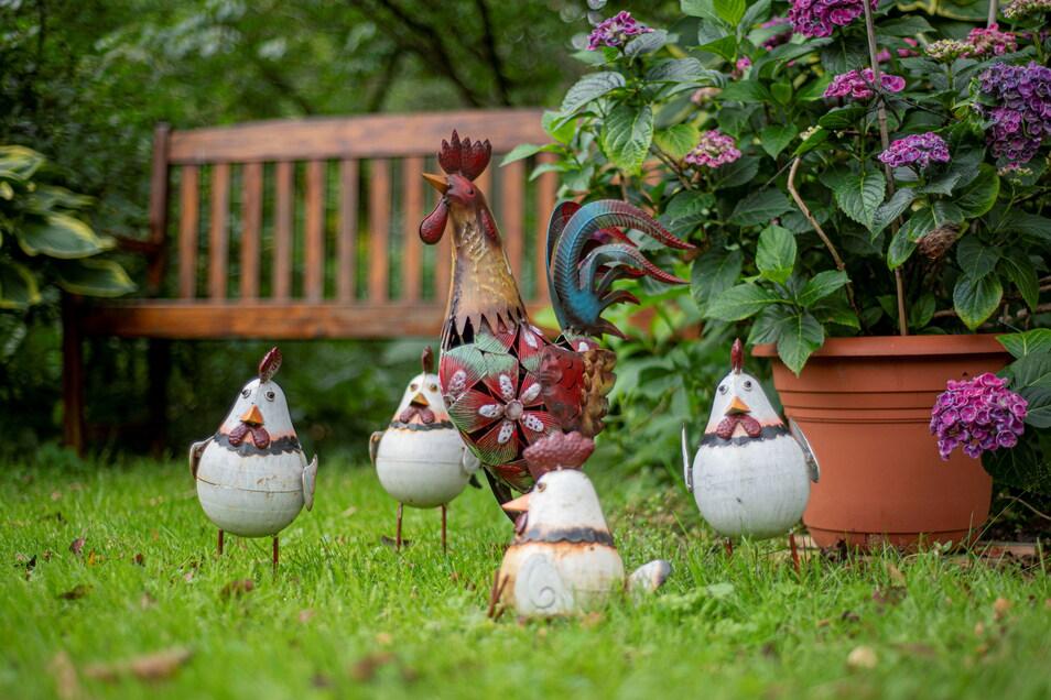 Ein Hahn geht mit seinen Hühnern im Garten spazieren - aus Keramik.