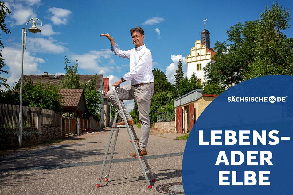 Olaf Lier, der Chef des Coswiger Ordnungsamtes, steigt in Brockwitz auf die Leiter und zeigt, wie weit die Häuser auf der Niederseite des Elbdorfes angehoben werden sollen.