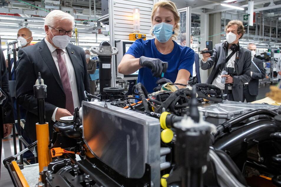 Bundespräsident Frank-Walter Steinmeier informiert sich am Arbeitsplatz von Jessica Göhl, Mitarbeiterin im VW Werk Zwickau, über die Montage des Antriebsstrangs für die Elektrofahrzeuge ID.3 und ID.4.