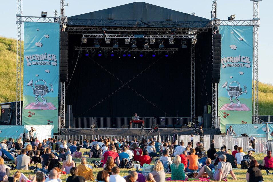 Es durftet nach Heu und Sommer: Auf Picknickdecken im 1,50-Meter-Abstand verfolgen 1.000 Leute das ausverkaufte Picknick-Konzert in der Dresdner Rinne, das gleichzeitig eine Lesung ist.