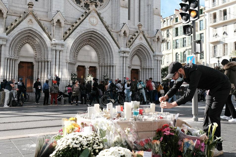 Frankreich, Nizza: Ein Mann zündet vor der Notre-Dame-Basilika zwischen Blumen eine Kerze an. Nach der brutalen Attacke wollen Anti-Terror-Ermittler herausfinden, ob der Tatverdächtige möglicherweise von Komplizen unterstützt wurde.