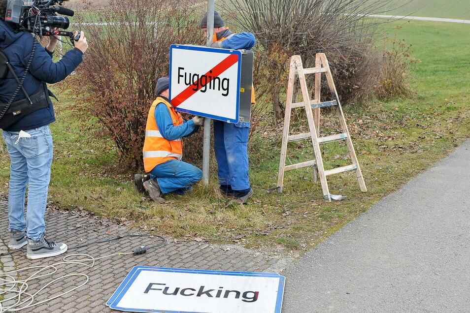 """Arbeiter bringen das neue Ortschild an. Der Ort mit rund 100 Einwohnern, der wegen der Namensgleichheit mit den obszönen englischen Begriff """"Fucking"""" immer wieder gestohlene Ortsschilder zu beklagen hatte, heißt ab dem 1. Januar 2021 Fugging."""