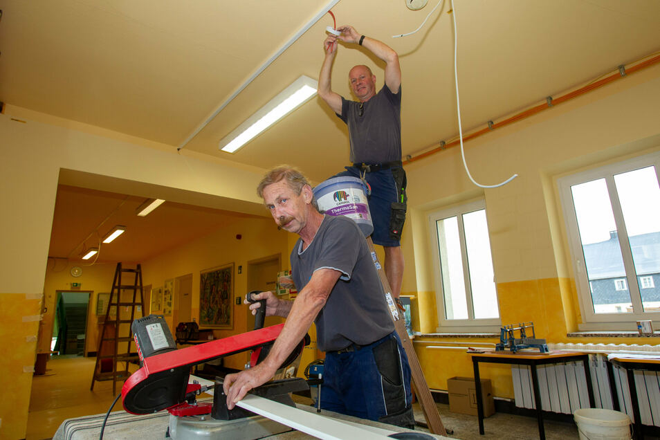 Joachim Nowotnick (links) sägt einen Kabelschacht und Andreas Boraschke (rechts) montiert einen Brandmelder in einem Klassenzimmer.