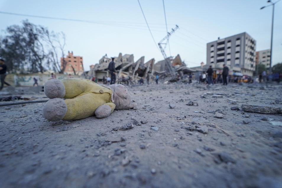 Ein Teddy liegt auf einer staubigen Straße in Gaza-Stadt, im Hintergrund stehen Palästinenser bei Trümmern von Gebäuden, welche bei israelischen Luftangriffen auf die Stadt zerstört wurden.