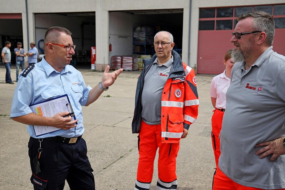 Kreisbrandmeister Ingo Nestler (li.) spricht mit Johannitern vor der Abfahrt aus dem FTZ in Glaubitz.