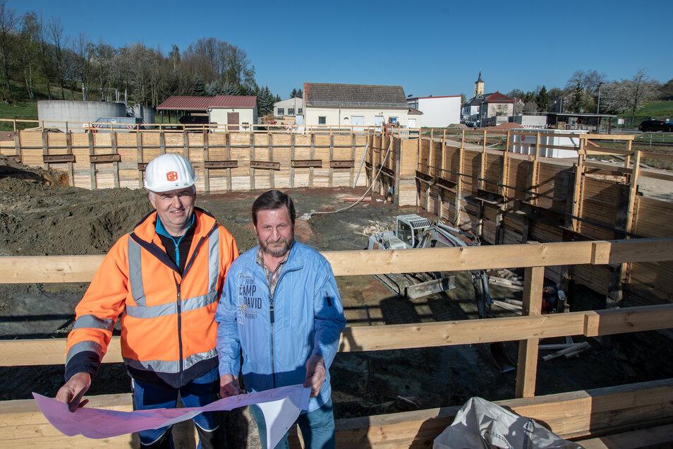 Reiner Müller (rechts), Technischer Leiter beim AZV Untere Zschopau, und Polier Thomas Richter stehen vor der riesigen Baugrube im Klärwerk Hartha.