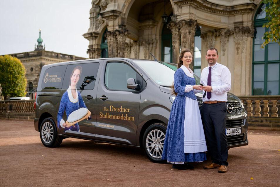 Christian Schleicher vom Autohaus Dresden übergibt als Mobilitätspartner des Stollenmädchens einen Opel Zafira Life.
