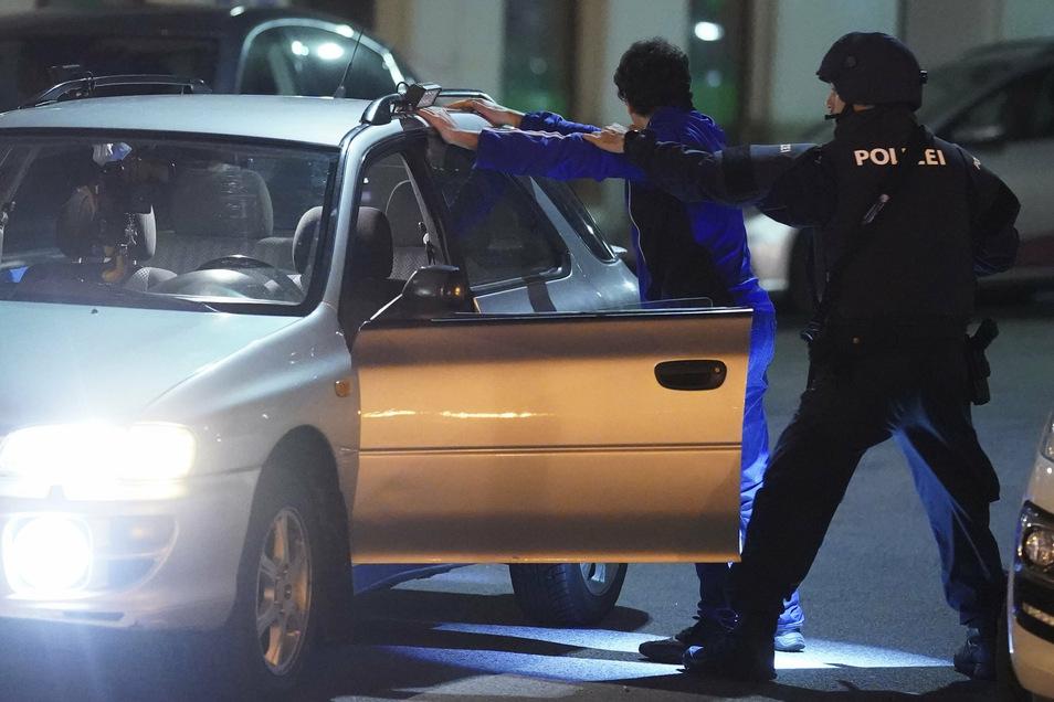 Schwerbewaffnete Polizisten kontrollieren in der Wiener Innenstadt an einem Auto eine Person.