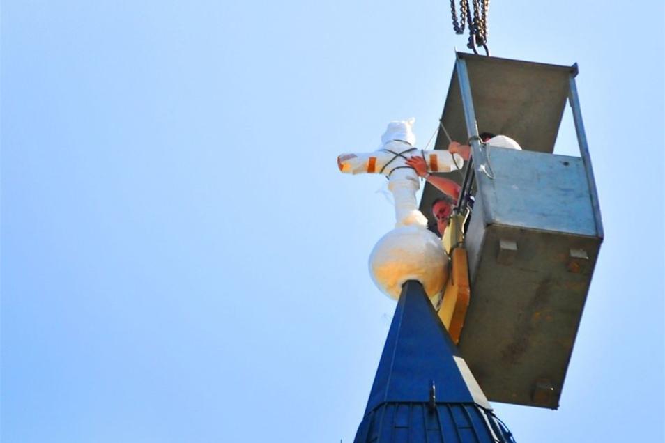 Nachdem sie innen befestigt wurde, folgte die Turmkugel und das 30 Kilogramm schwere goldene Kreuz.